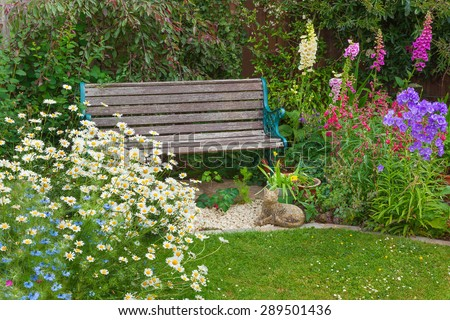 Cottage garden with bench and mixed flowers. - stock photo