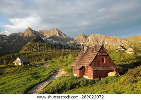 Cottage in a valley surrounded by the Tatra Mountains. - stock photo
