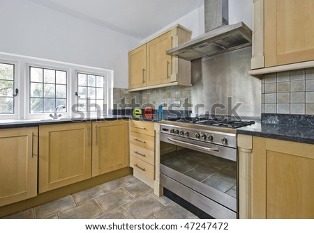 cottage style kitchen with massive stainless steel oven and ceramic eat sign - stock photo