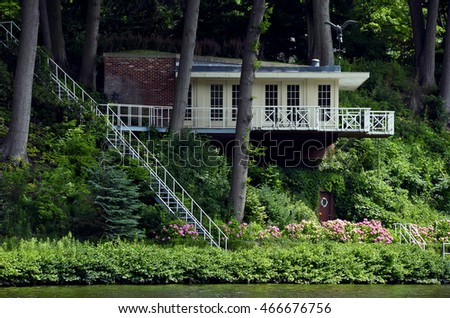 cottage with stairway in woods overlooking river