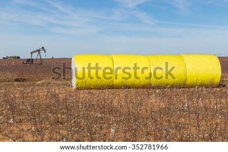 Cotton bales in bright yellow  protective wrap in harvested cotton field with pumping oil rig in background.