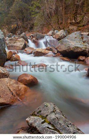 Cotton candy soft water with red rocks next to a tranquil forest - stock photo