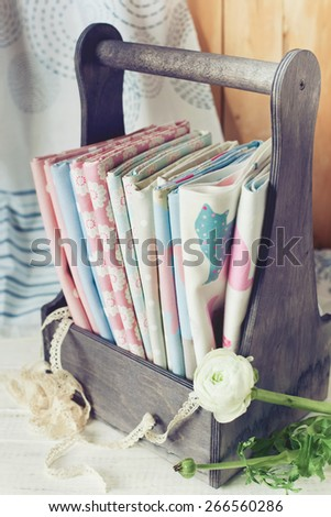 Cotton fabrics bundle in a wooden box. Home sewing and handmade hobbies concept. Toned photo, shallow focus. - stock photo