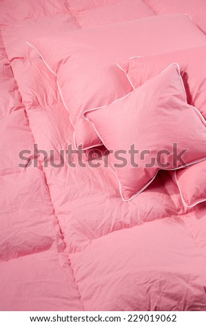 Cotton pink fluff duvet with pillows without cover, eiderdown filled with fluff or feathers. Vertical orientation, nobody.