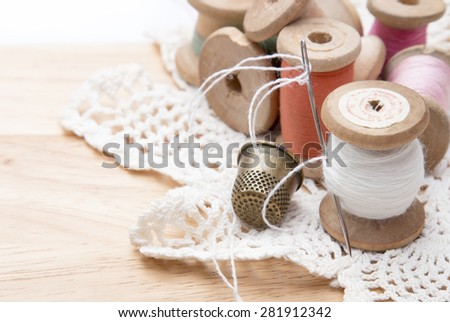 cotton thread for sewing, wound on a wooden spool, white lace and a metal thimble, vintage,on wooden background - stock photo