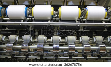 Cotton Yarn Production in a Textile Factory. Textile fabric manufacturing machines in work. - stock photo