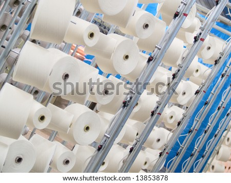 Cotton yarn spools (bobbins) in a textile factory - stock photo