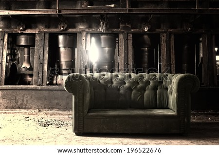 Couch in an abandoned industrial background  - stock photo
