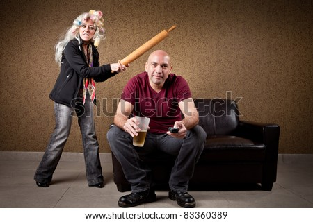 Couch potato and angry wife - stock photo