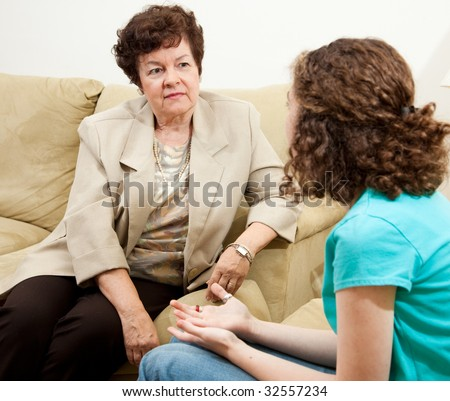 Counselor listening with sympathy to a teen patient. - stock photo