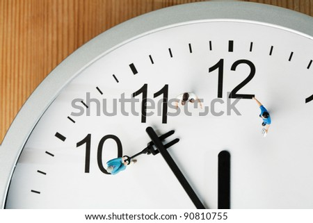 Countdown To Midnight And New Year. A team of miniature toy figurines tries to push the minute hand to midnight, closeup on a portion of a clock face. - stock photo