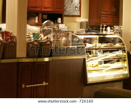 Counter in coffee bistro with bagels under glass and busy clerk filling orders. - stock photo