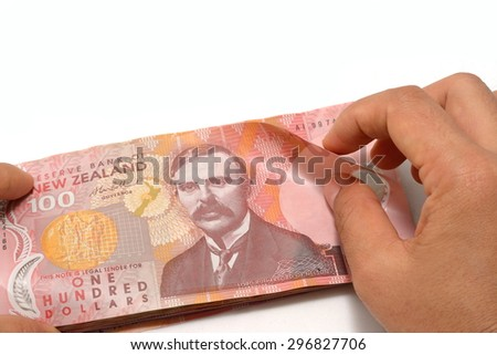 Counting dollar notes in New Zealand currency on white background - stock photo