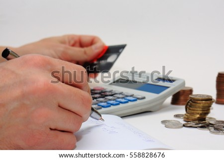 Counting money using calculator, credit card, pen, paper and coins hands