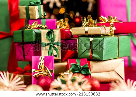 Countless Christmas gifts stacked up. Shallow depth of field. Blurred stars and baubles in front and rear. Bokeh over black background. Tightly framed. Focus on golden present with green bow. - stock photo