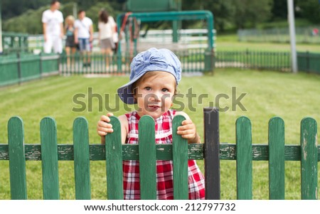 Country baby girl near a wooden fence  - stock photo