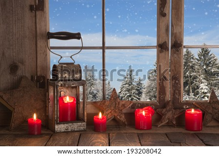 Country Christmas decoration: wooden window decorated with red candles and rustic lantern. View to the mountains in the alps. - stock photo