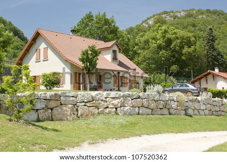 Country cottage house and car parking in front of garage - stock photo