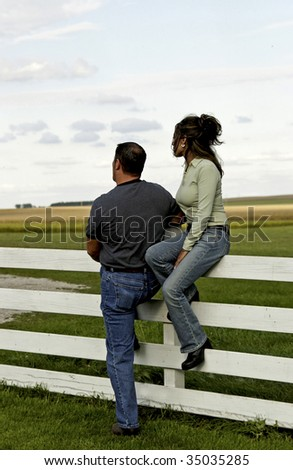 country couple against fence