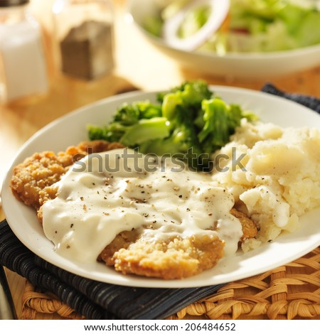 country fried steak with southern style peppered milk gravy - stock photo