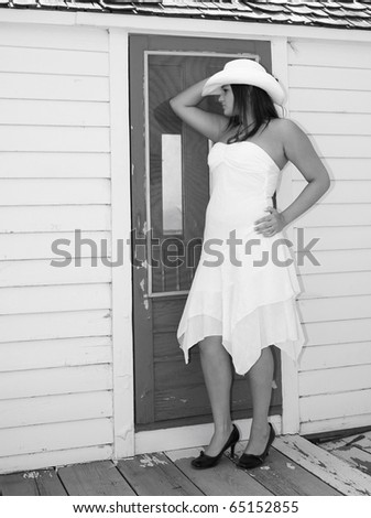Country girl on the back porch, dress and cowboy hat.