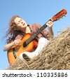Country girl playing guitar at haystack - stock photo