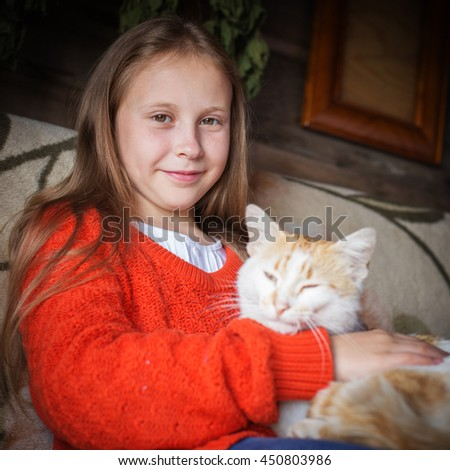 Country girl stroking a cat. - stock photo