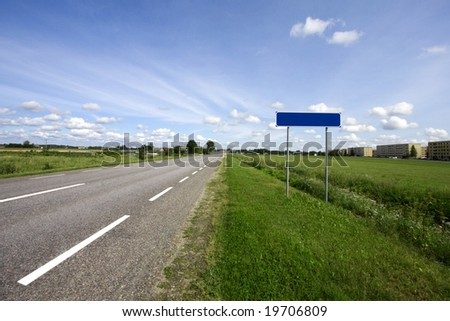 Country highway and blank city name sign. Blue sky with clouds and green grass. - stock photo