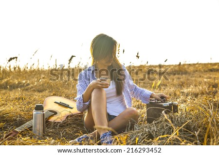 Country hippie girl sitting near acoustic guitar at wheat field drinking black coffee from a mug thermos of relying on the old retro brown leather vintage suitcase - stock photo