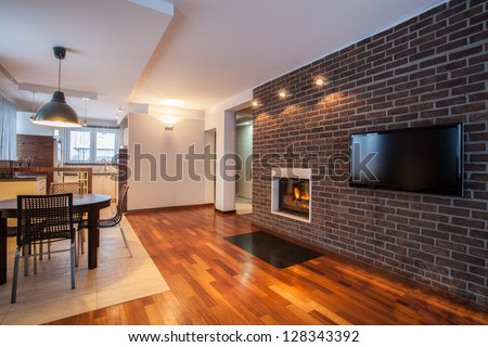 Country home - dining room with brick wall and fireplace - stock photo