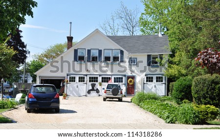 Country Home with Two Cars in Driveway sunny blue sky day - stock photo