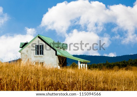 Country house in the American Southwest with tall golden grass and hills, blue sky and white puffy clouds. - stock photo