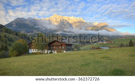 Country houses at foothills of a rocky mountain range lighted up by golden sunlight at sunset ~ Beautiful scenery of a small village by Hochkonig Mountains between Dienten and Muhlbach, Austria Europe - stock photo