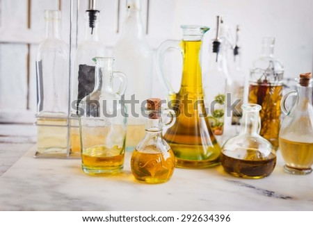 Country kitchen Still life. various bottles with raw olive oil with herbs and vinegar over on a marble rustic table. Vintage style. - stock photo