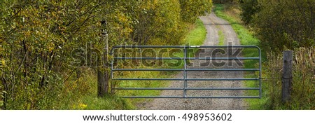 Country lane / driveway with a metal gate