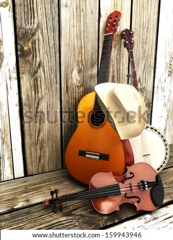 Country music background with stringed instruments. Guitar, banjo , violin and a cowboy hat leaning against a wood fence.  Room for text or copy space. - stock photo