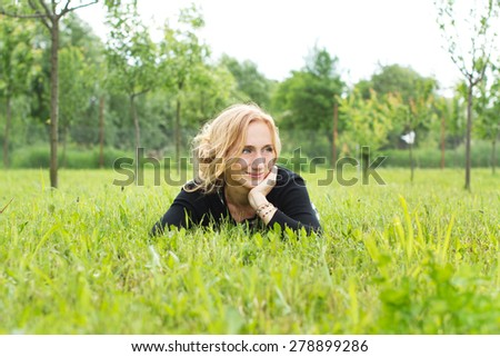 Country pretty woman lying in the grass - stock photo
