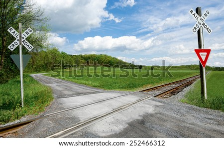 Country Railroad Crossing:  A narrow gravel road crosses a set of railroad tracks in rural Virginia.  - stock photo