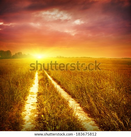 Country road and dramatic sunset. - stock photo