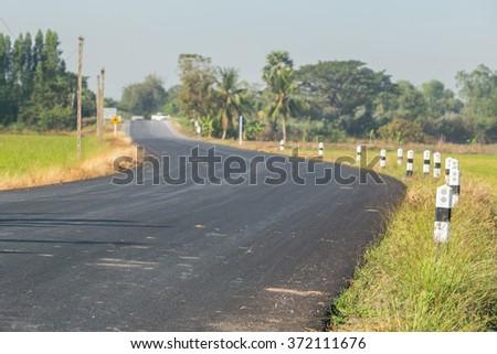 Country Road and pillar Through Farmland , Thailand - stock photo