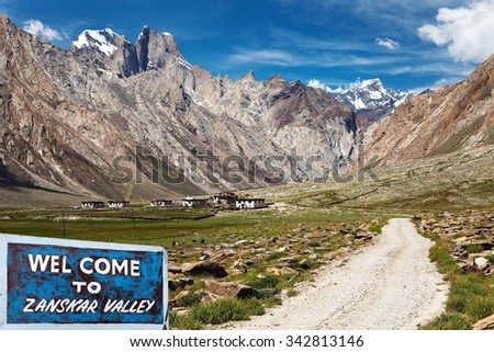 Country road and village in Suru valley and signpost Welcome to Zanskar valley, road from Kargil to Padum, Zanskar valley, Ladakh, Jammu and Kashmir, India - stock photo