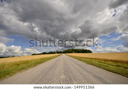 Country road in a cloudy agricultural land - stock photo