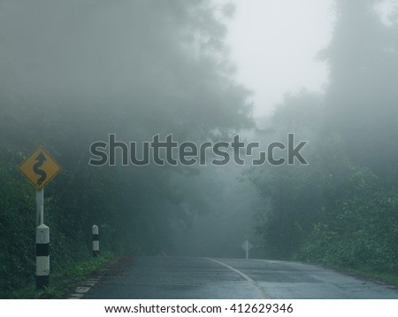 Country road in a forest on a foggy morning and traffic sign - stock photo