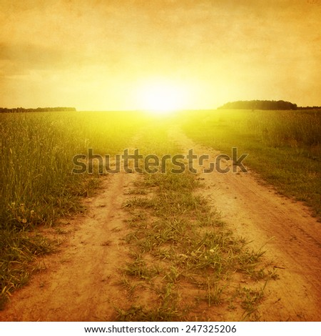Country road in the field at sunset in grunge and retro style. - stock photo