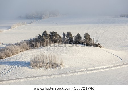 Country road through a wintry landscape - stock photo