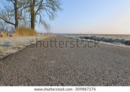 country road through fields in winter - stock photo