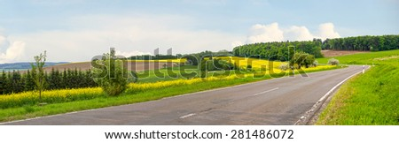 country road through hilly german landscape and blooming rape field - stock photo