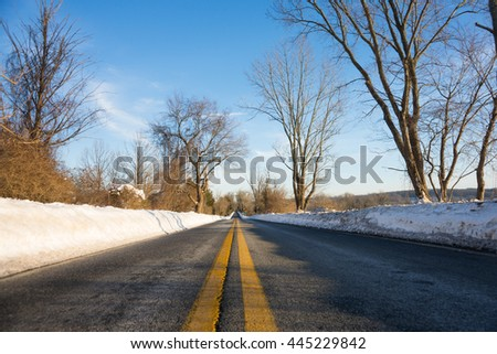 Country Road Through Paved Snow On a Sunny Winter Day
