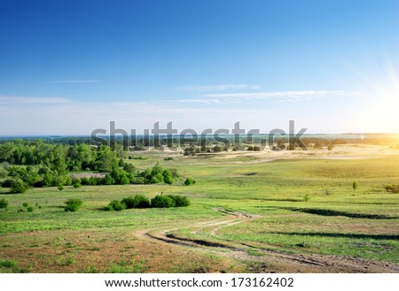 Country road through the plain at sunrise - stock photo