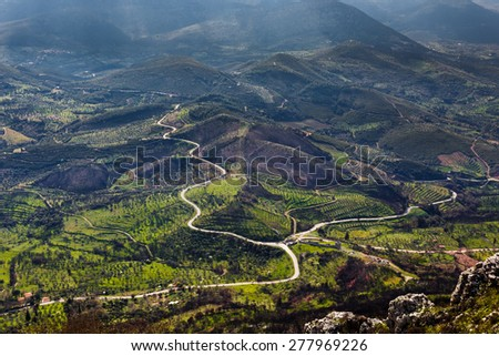 Country road through vegetation with sun rays lighting parts of the natural landscape in greece - stock photo